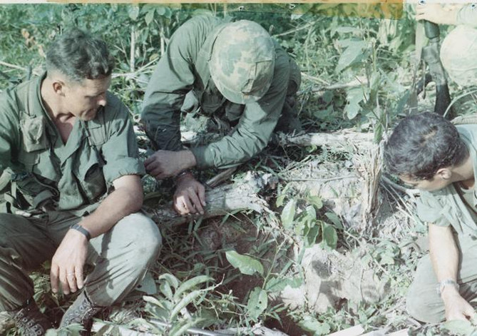 The mission of C Company, 1st Battalion, 5th Mechanized Infantry, 2nd Brigade, 25th Infantry Division was to sweep through the Filhol Plantation in search of fleeing Viet Cong units. Members of the units look into a Viet Cong tunnel awaiting the return of their tunnel rat.   Source: VA029806, Robert Lafoon Collection, The Vietnam Center and Sam Johnson Vietnam Archive, Texas Tech University