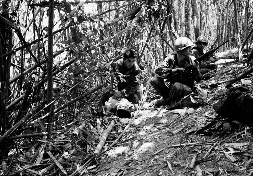 Infantrymen with the U.S. 101st Airborne Division provide security for a medic as he administers first aid for a wounded soldier, May 19, 1969. The rifleman, one of 200 Americans wounded in fighting for Dong Ap Bia, lies in a tiny clearing in the bamboo on the side of the mountain.   Source: AP Photo