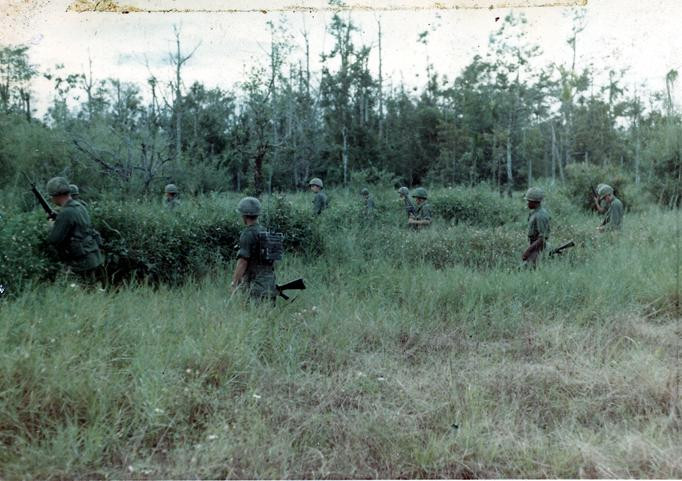 The mission of C Company, 1st Battalion, 5th Mechanized Infantry, 2nd Brigade, 25th Infantry Division was to sweep through the Filhol Plantation in search of fleeing Viet Cong units. Soldiers sweep through a brushy terrain in search of Viet Cong.  Source: VA029825, Robert Lafoon Collection, The Vietnam Center and Sam Johnson Vietnam Archive, Texas Tech University