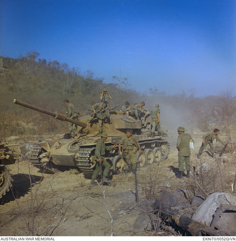 """A Centurion tank of A Squadron, 1st Armoured Regiment, disgorges its load of soldiers in the mountains area of southern Phuoc Tuy Province. The troops, of 8th Battalion, The Royal Australian Regiment (8RAR), were moving into the hills to mop-up after a battle with a Viet Cong (VC) company. Identified, second from right is 37811 (Temporary) Major Malcolm Charles """"Mal"""" Peck.  Centurion tanks of 1 Armoured Regiment provided vital fire support throughout Operation Hammersley. The tanks' main guns were particularly useful in dealing with enemy bunkers.  Source: Australian War Memorial item no. EKN/70/0052Q/VN"""