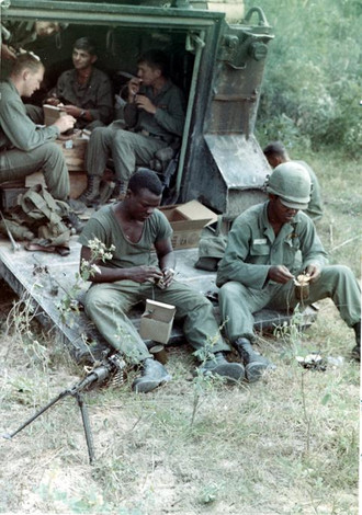 The mission of C Company, 1st Battalion, 5th Mechanized Infantry, 2nd Brigade, 25th Infantry Division was to sweep through the Filhol Plantation in search of fleeing Viet Cong units. During a break in the sweep, soldiers sit inside and on the ramp of an M113 Armored Personnel Carrier and eat C-rations for lunch.  Source: VA029807, Robert Lafoon Collection, The Vietnam Center and Sam Johnson Vietnam Archive, Texas Tech University