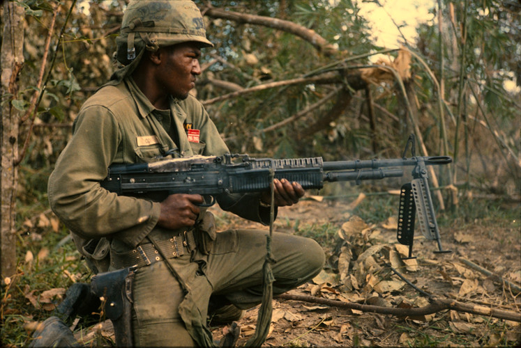 """On 8 January 1967, PFC Milton L. Cook (Baltimore, MD) fires his M60 machine gun spraying a tree line. The platoon received sporadic sniper fire from the tree line earlier. PFC Cook was one of many Soldiers from """"C"""" Company, 1st Battalion, 5th Mechanized Infantry, 25th Infantry Division on a search and destroy mission. The mission was a part of Operation """"Cedar Falls"""" conducted in and around the Filhol Plantation near Cu Chi, Republic of Vietnam.  Source: National Archives photo no. 100310262"""