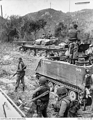 Australian troops prepare to sweep through thick scrub in the Long Hai mountains in South Vietnam during Operation Hammersley. The men, of 8th Battalion, The Royal Australian Regiment (8RAR), had clashed with a strong Viet Cong force in the area on 18 February 1970. Since then the mountains had been pounded continually by air strikes, naval bombardment, and artillery fire. This time the soldiers were more than prepared: every man was wearing a flak jacket and steel helmet, and leading the sweep were Centurion tanks and armored personnel carriers.  Source: Australian War Memorial item no. FAI/70/0112/VN