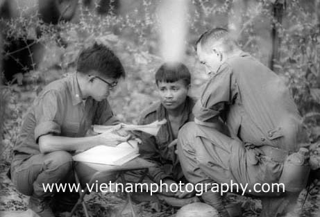 A Viet Cong prisoner captured near Quần Lợi on July 10, 1966, is interrogated by an American soldier and a Vietnamese translator. The VC was captured by soldiers from the 1st Infantry Division.  Used with permission of the photographer.