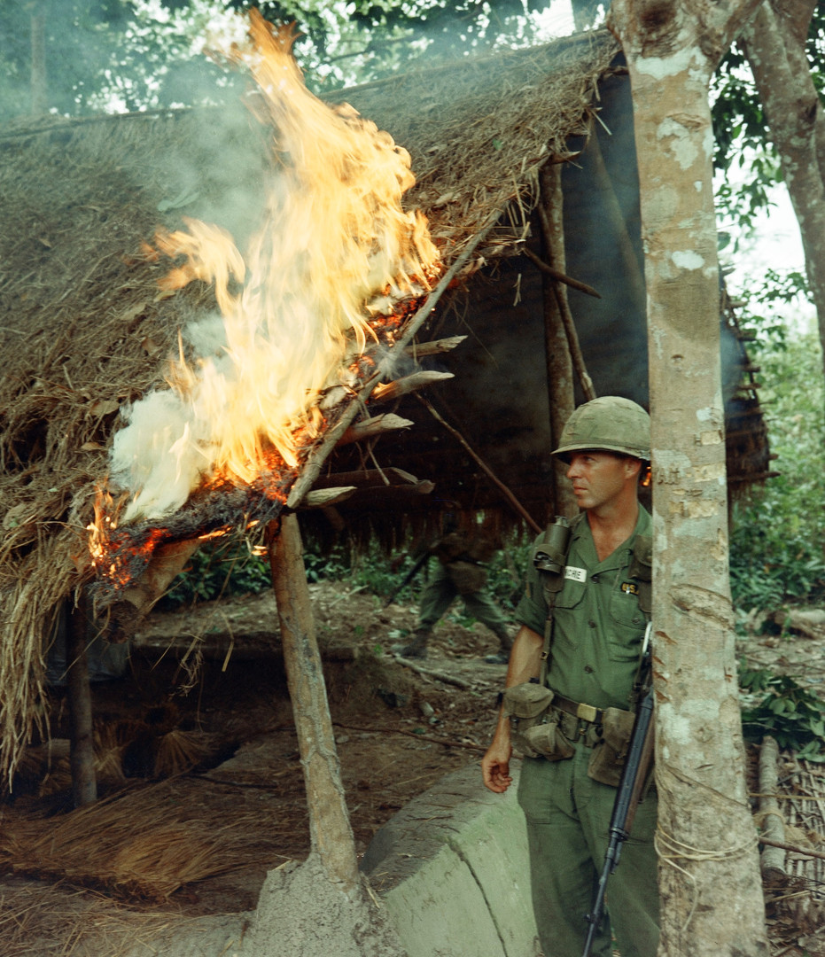 During Operation Crimp near Bien Hoa, RVN, the 28th Infantry, 1st Infantry Division found a Viet Cong village while on a search and destroy mission SGT Richard McConchie watches a fire he started. This structure was one of many found inside the village and destroyed.  Source: National Archives photo no. 66955097