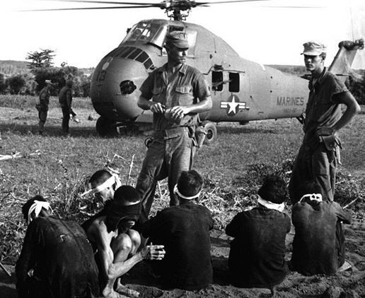 Viet Cong prisoners await being carried by helicopter to rear area after Operation Starlite.
