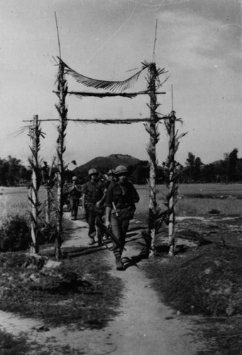 Operation Union--Lance Corporal William M. Collins, Echo Company, 2nd Battalion, First Marines, leads a column of Marines under a Viet Cong propaganda gate.  Source: National Archives photo no. 26387675