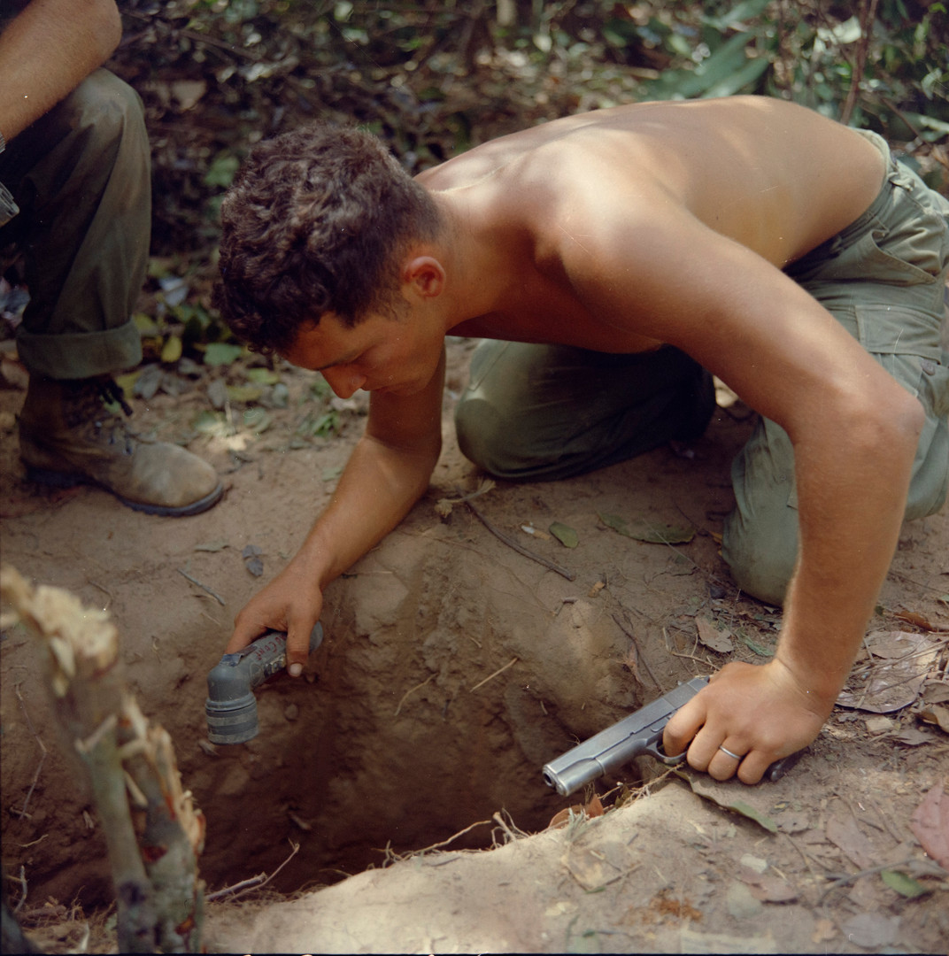 On 24 January 1967, SGT Ronald A. Payne (Atlanta, Ga) Squad Leader, Company A, 1st Battalion, 5th Mechanized Infantry, 25th Infantry Division, checks a tunnel entrance before entering. This was one of several tunnels found in the Cu Chi, Republic of Vietnam area. This tunnel was found while the company was conducting a search and destroy mission as a part of Operation Cedar Falls in the Hobo Woods area.  Source: National Archives photo no. 100310284