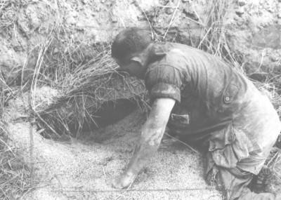 Army officer digging into tunnel entrance.  Source: VA003022, Douglas Pike Photograph Collection, The Vietnam Center and Archive, Texas Tech University