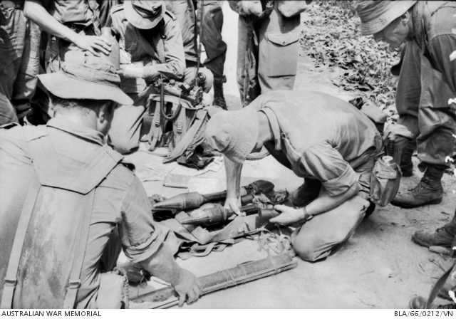 1966-03-18. Australian soldiers examine anti-tank missiles captured from the Viet Cong during Operation Rolling Stone in the Ben Cat area. A home-made Bangalore torpedo made from hollow bamboo and intended for use against barbed wire entanglements is in the foreground.  Source: Australian War Memorial item no. BLA/66/0212/VN