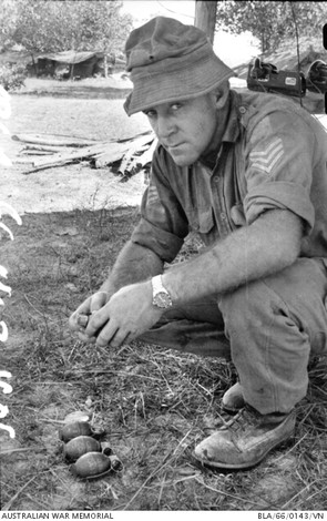 1966-02-20. Wary look from Sergeant (Sgt) Gus Sant of Sydney, NSW, as he examines a hand grenade captured from a Viet Cong suspect during Operation Rolling Stone near Ben Cat. Sgt Sant, an Army engineer, is serving with the Australian force based at Bien Hoa.  Source: Australian War Memorial item no. BLA/66/0143/VN