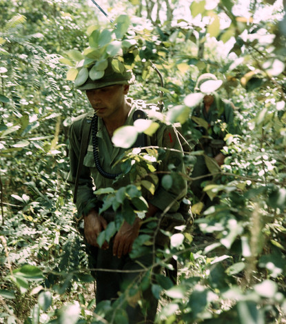 Operation Crimp was a search and destroy mission conducted by the 1st Infantry Division near Bien Hoa, RVN. CPL Ralph Nicholls (Fremont, CA) moves through dense jungle area in pursuit of Viet Cong. Cpl Nicholls was a Radio Telephone Operator (RTO) with the 28th Infantry, 1st Infantry Division.  Source: National Archives photo no. 66956458
