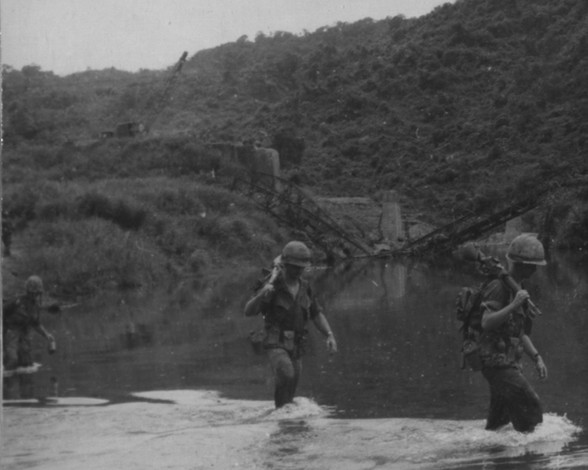 """17SEP66. Operation Prairie--Company """"E"""", 2nd Battalion, 7th Regiment cross a river 3 miles west of Cam Lo, as engineers work on a bridge in the background.  Source: National Archives photo no. 26387407"""