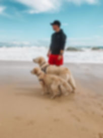 James Coffey at te beach with his two dogs Coopr and Piper looking into th distance