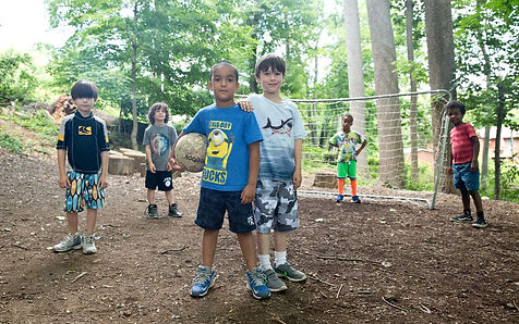 boys play soccer in woods