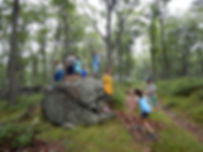 campers climb large rocky outcropping