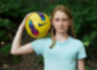girl with soccer ball on shoulder