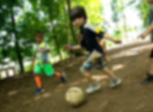 kicking soccer ball in forest