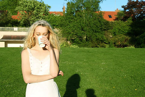 blonde bride in white dress and tiara drinks at hampstead heath
