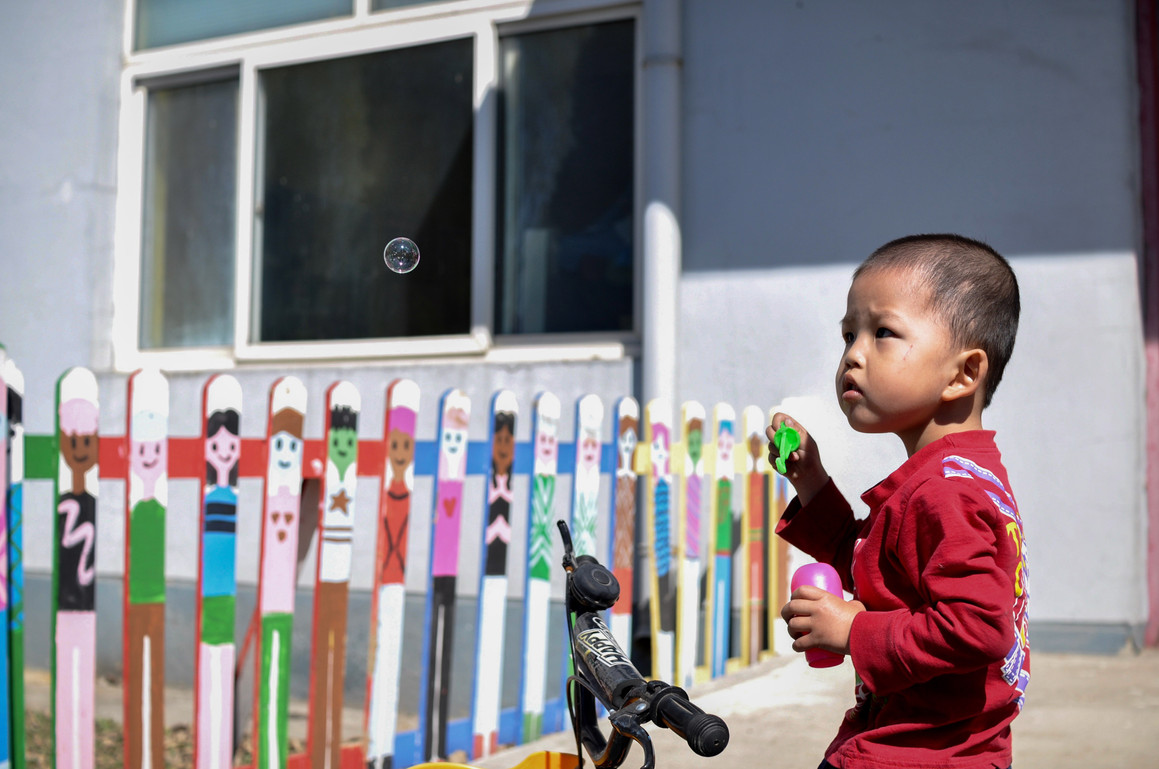 One of the orphan children blowing bubbles during play time.
