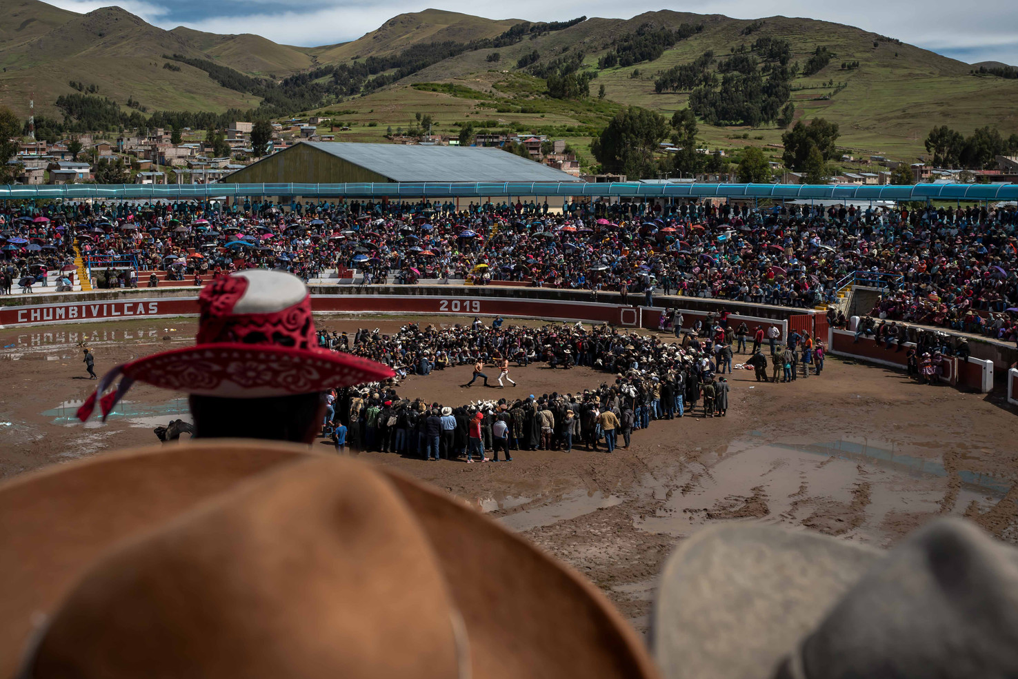 Thtree of the three thousand Takanakuy spectators filling the arena of Santo Tomas around a center fight.