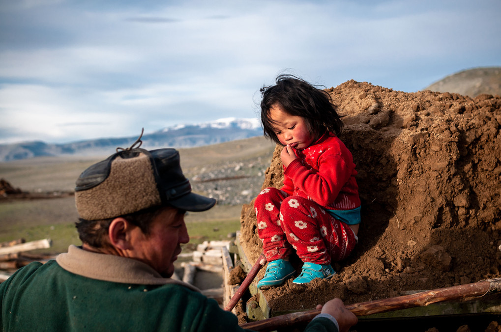 Beken and his daughter, Esen's older rother and niece help load dirt from a nearby pit. The dirt is mixed with water to act as mortar and seal cracks within the logs.