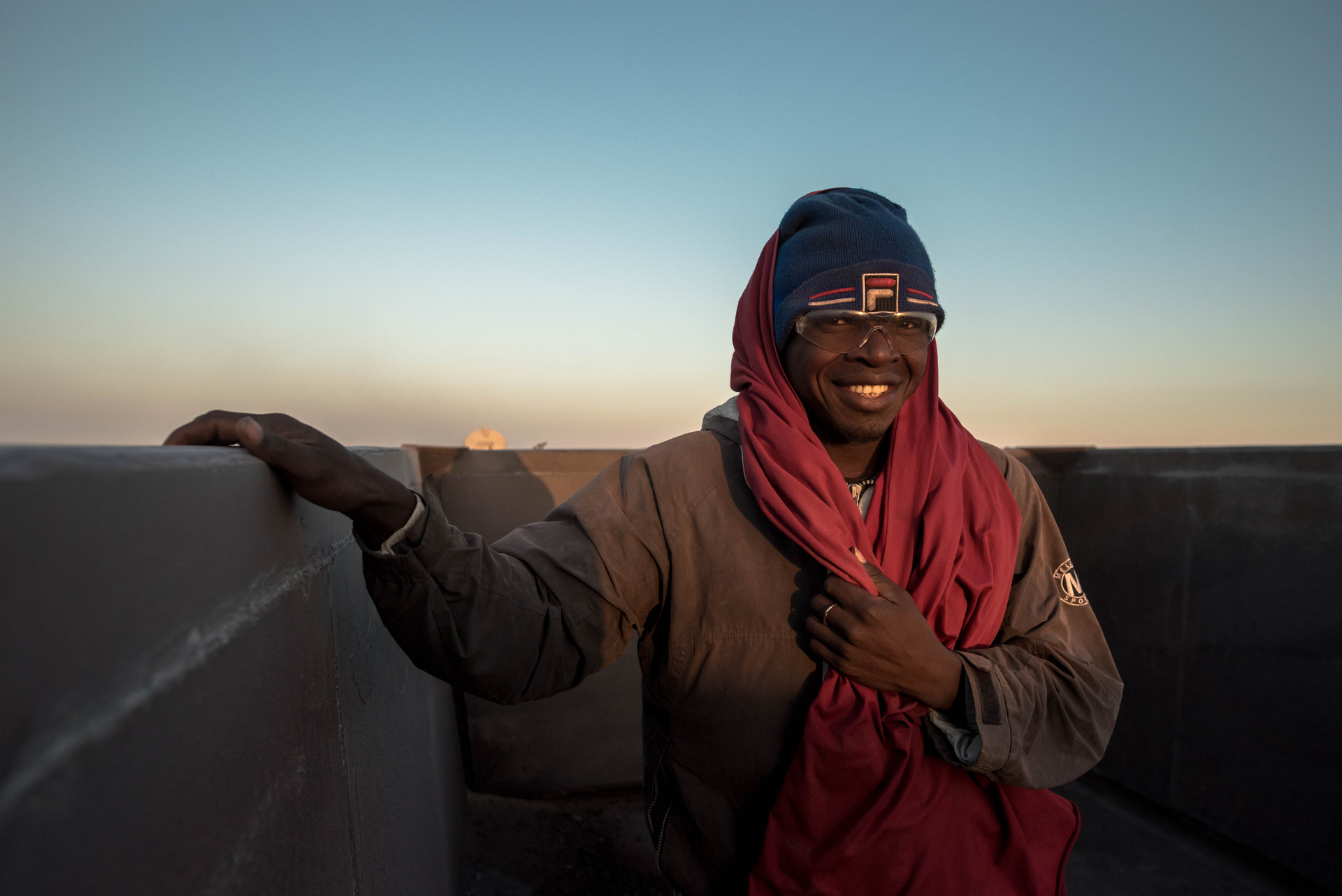 After battling a long cold night, a Malian mine worker continues his journy on his way back to the iron-ore mines.