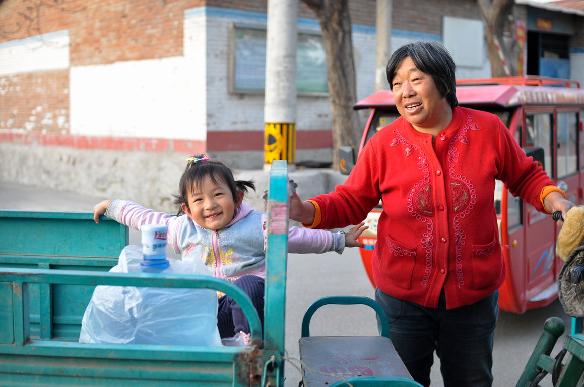 A nanny and her kids take a ride down to the grocery store in a nearby village. Each nanny overlooks the motherly duties of 4 kids.