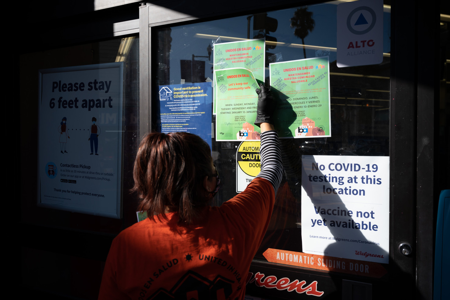 Glenda Cifuentes, who works as a cashier in a restaurant, volunteers to put up fliers for encouraging essential workers within the Latino Cultural District of San Francisco to get free low barrier COVID-19 testing.