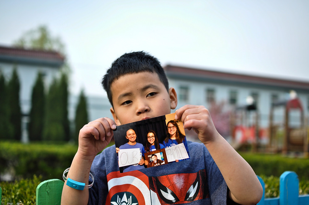 Nine year old orphan Shao Dong shows off a photo of his newly matched family posing with a picture of him. Suffering from an imperforate anus and living at a Chinese foster home where he is the oldest child by 5 years - he has been matched previously but unfortunately returned due to his condition.