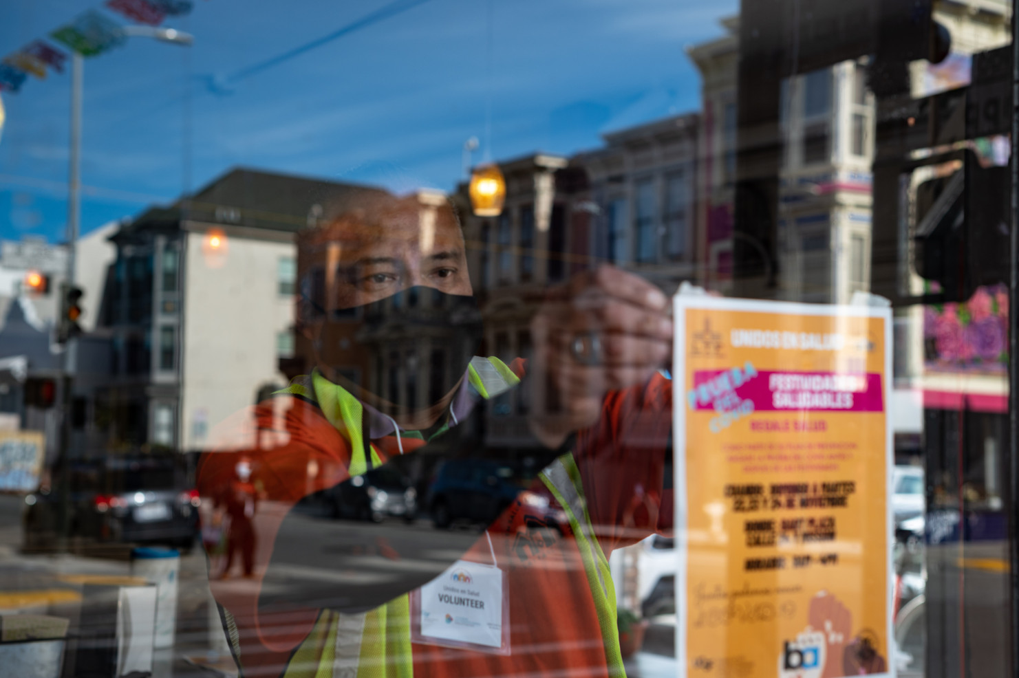 Marco Carballido, a volunteer with Unidos en Salud puts up a flier in the window of a local business notifying the Latinx community of free low barrier COVID-19 testing.