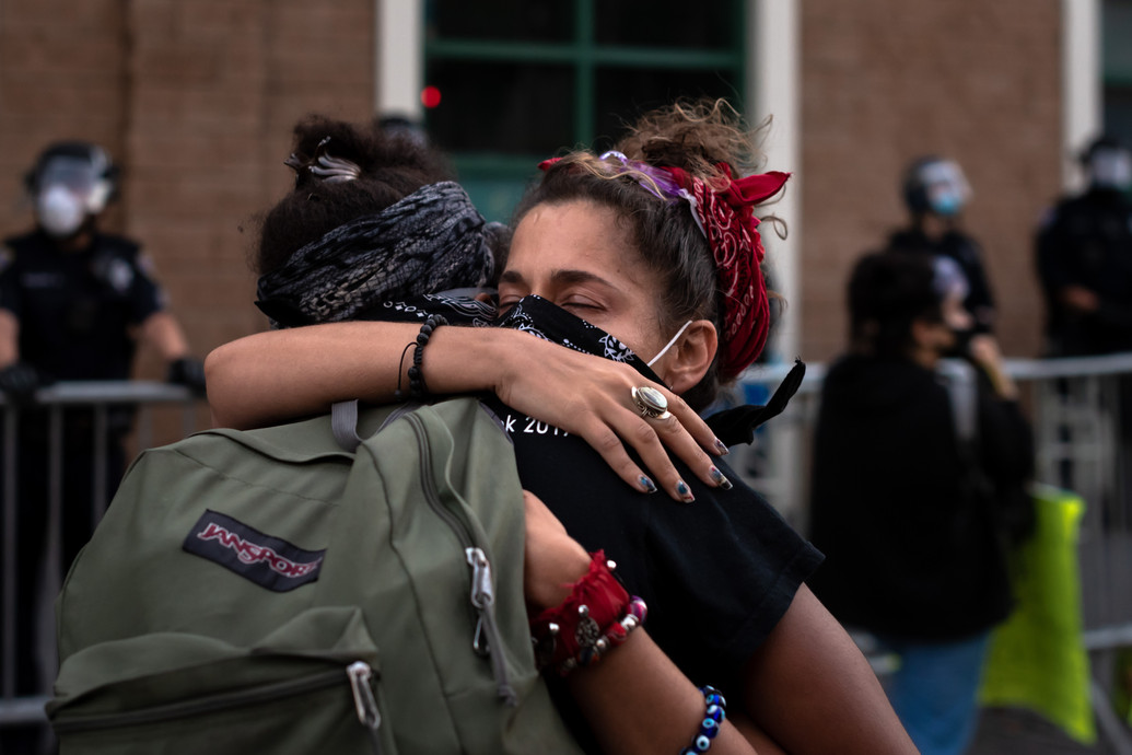 Black Lives Matter protestors Lala and Lita embrace in front of Mission Police Station as the last remaining members of a massive 20,000 people protest for police brutality in the Mission District of San Francisco. June 3, 2020.