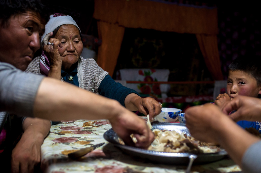 """Dinner is served after sunset and all the animals are back safe for the day. The """"all hands"""" plate is a communal plate consisting of goat meat and boiled flour sheets - the entire family share the plate using only their hands."""