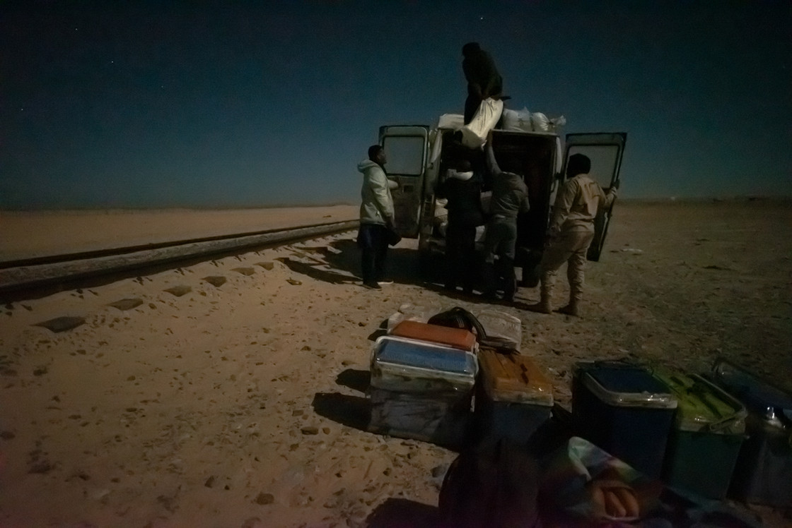 Locals arrive with a van full of goods to be loaded onto the empty train carts. For many, the iorn-ore train is the only means of transportation in and out of the Sahara Desert.