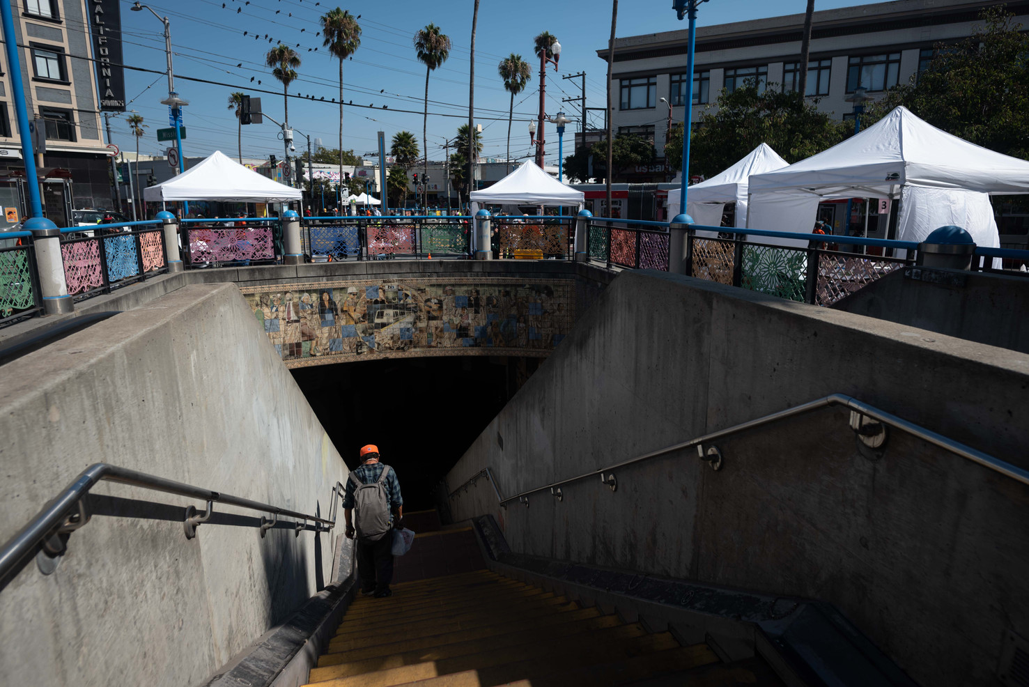 A service worker enters 16th Mission Bart station on his way to work after being tested for COVID19 at the pop up test site strategically placed around the station for commuters. The series of low barrier testing for essential workers is put on by Unidos en Salud - a partnership between UC San Francisco Medical School and Latino Task Force for COVID19. Marginalized Latino and Black communities suffer disproportionately from the highest rates of infection as they work essential jobs to keep the country running during quarantine.