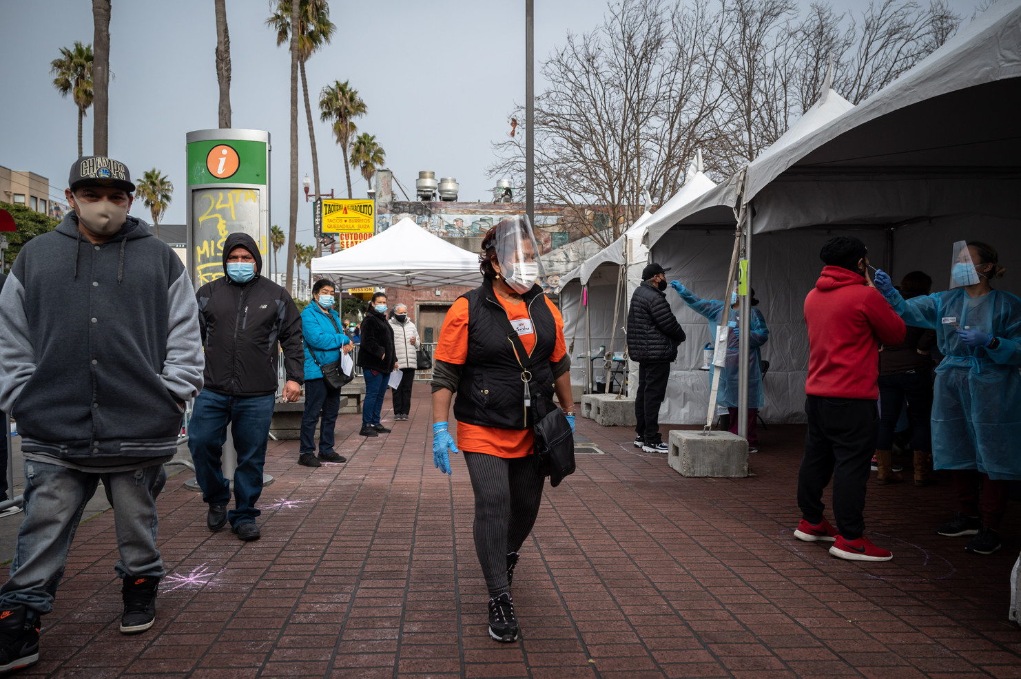 Unidos En Salud volunteer coordinator Lourdes Lozano guides Latino community members lined up waiting to be tested at a free pop up COVID-19 test site in front of 24th Mission Bart Station.