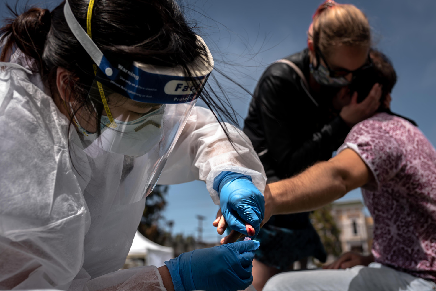 CCSF nusing student Audrey Jung collects blood samples from a squeemish George Kailas as he is comforted by his partner Emily Brunts during UCSF's mass COVID-19 testing study at Garfield Park. A comprehensive study of the virus's spread held by UC San Francisco researchers in partnership with San Francisco Department of Public Health and Zuckerberg General, mass testing is provided free of charge for the 5700 residents in a one mile square radius of the Mission district.