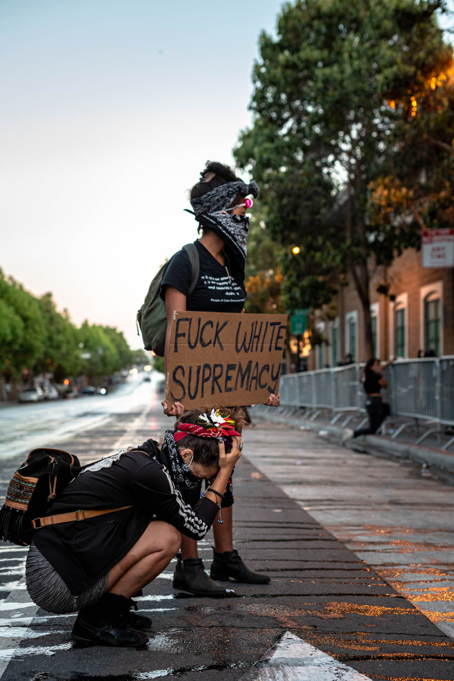 As the massive crowd of 20,000 Black Lives Matter protestors in San Francisco disband after curfew and cleaners hose down the street, passionate protestors Lala and Lita remain in front of Mission Police Station - exhausted yet still frustrated. June 3, 2020.