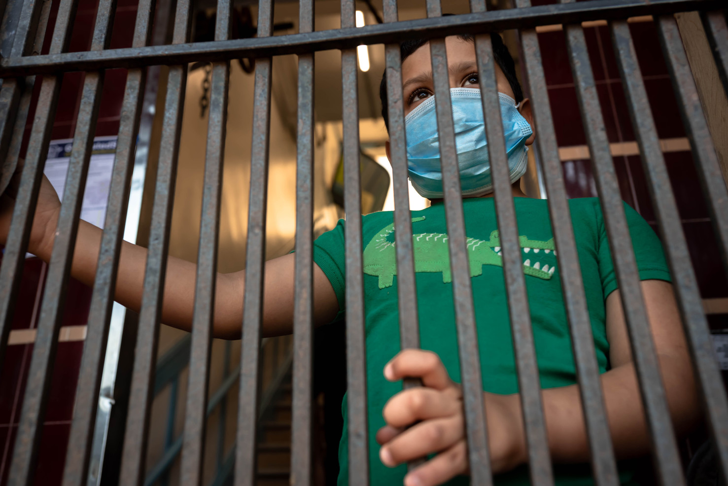 Anderson Garcia Hidalgo looks out the gate of his family's shared residence at the end of his family's self quarantine in the Latino Cultural District of San Francisco. His mother's partner was tested positive one month prior and has been supported by community programs such as testing, food deliveries, and medical care.