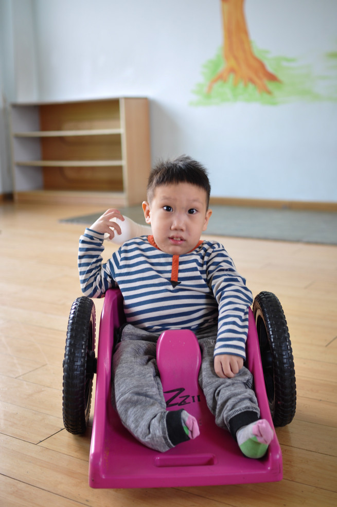 3 year old Ma Jia Cheng in his miniature wheelchair. He is unable to walk due to his club foot.