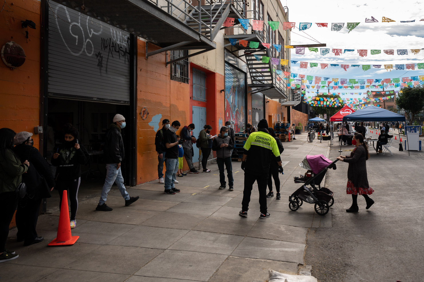 San Francisco Mission community members line up outside of the Latino Task Force Mission Resource Hub. Four days a week, the Mission Resource Hub provides free low barrier testing, vaccination registration, food distribution, and essential services such as employment and housing resources for hard hit community members.