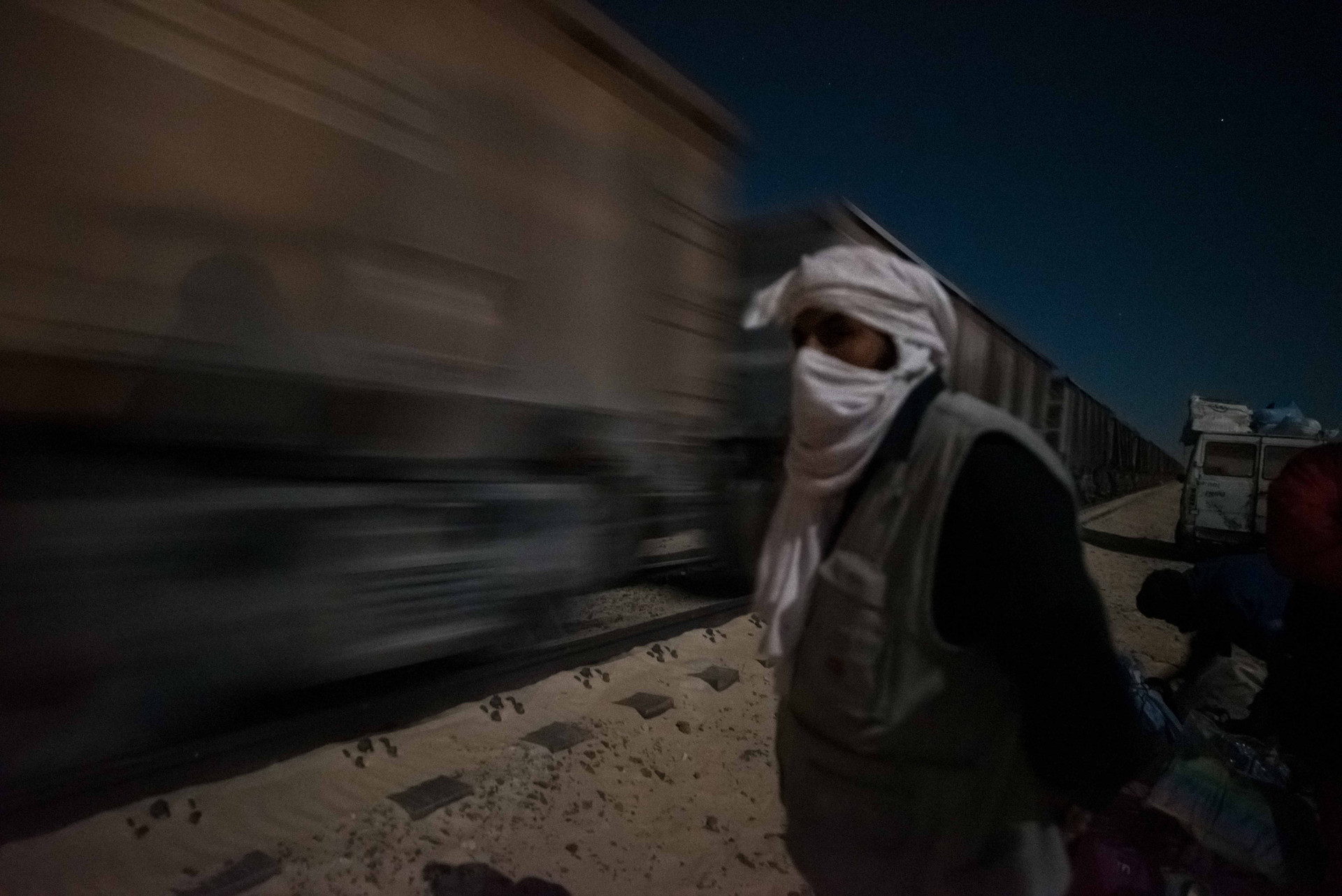 As the train arrives hitchhikers scramble to climb in and throw all the luggage over into one of the empty freight carts - the train takes off without warning. Goods brought along range from giant boxes of fish all the way to entire flocks of goats.