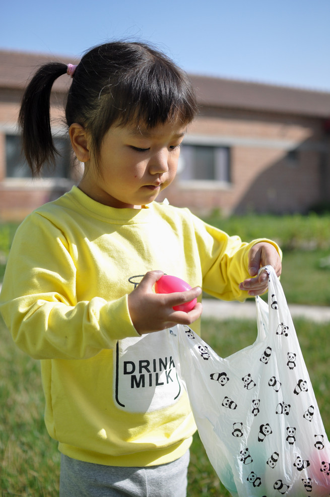 4 year old Si Chun searching for eggs during an Easter egg hunt put on by New Hope volunteers.