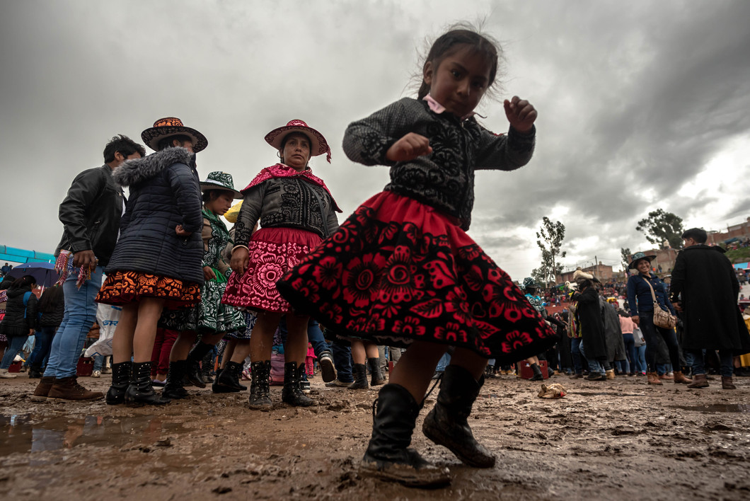 Sporadic downpours throughout the afternoon leave the floor muddy and slippery. The festival continue regardless with fighters slipping and struggling for balance. A girl dances and pretends to fight in the mud in between fights.