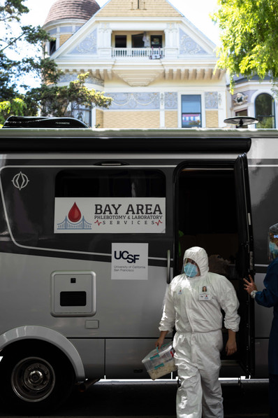 Yasmin Ramos, a phlebotomist with BAPLS (Bay Area Phlebotomy and Laboratory Services), steps out of a mobile test lab to provide in home testing for high risk community members unable to leave their houses.