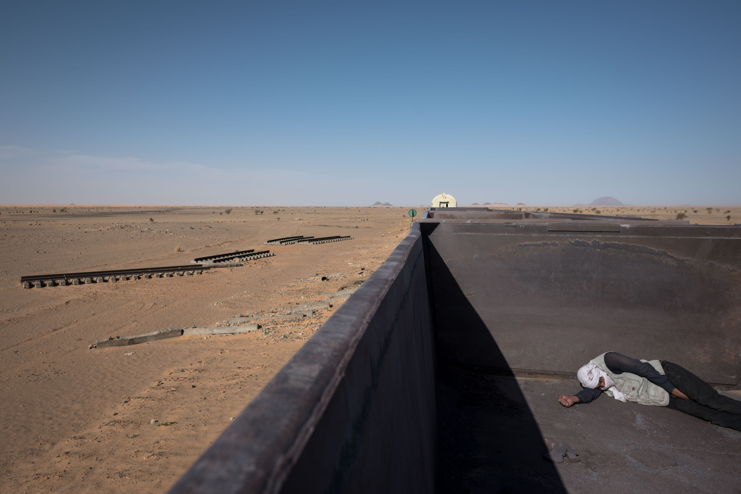 The sun quickly becomes overbearing to the hitchhikers as the open top train slowly moves along during it's 14 hour journey into the Sahara Desert.