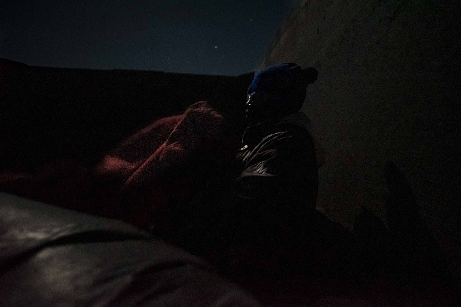 3am halfway into the night, a Malian mine worker screams in frustration at the constant whirlwind of freezing wind and sand pouring over the opentop of the cart.