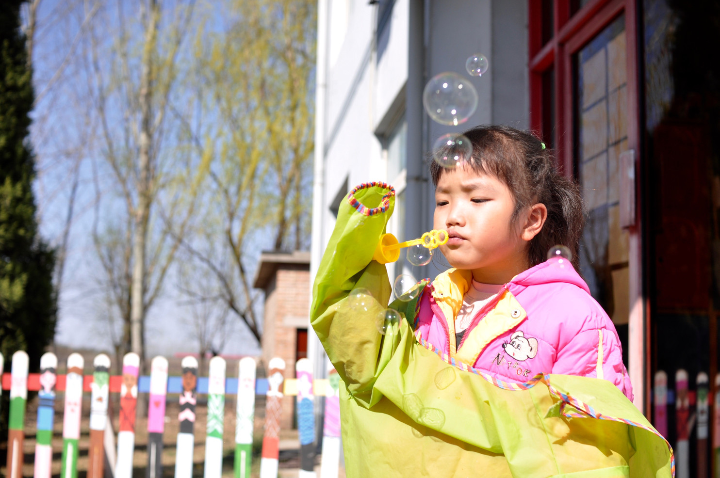 4 year old Si Chun blows bubbles during play time.