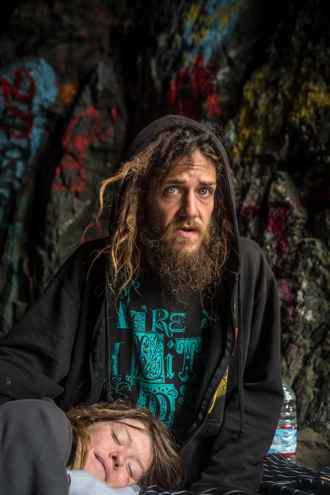 """Elena lays in Zach's lap inside a beach cave commonly used by the homeless. The two of them struggle with heroin addiction together on the streets of San Francisco.  """"We want people to see us as more than just addicts"""""""
