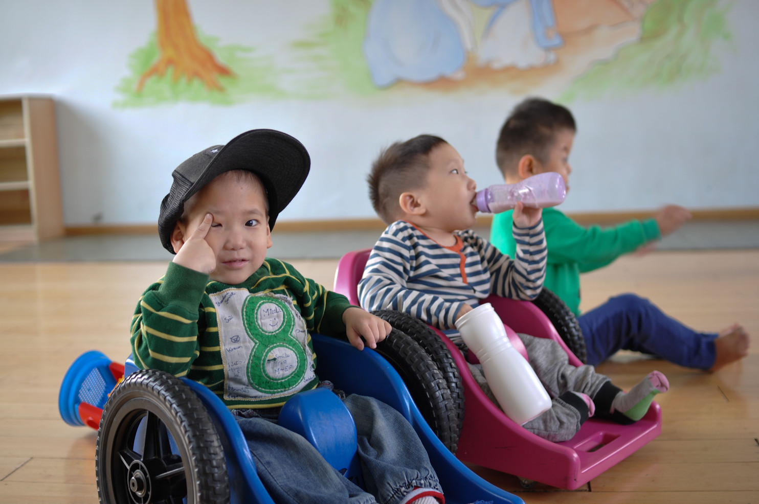 Children with spina bifida and club foot who are unable to walk ride in miniature wheelchairs.